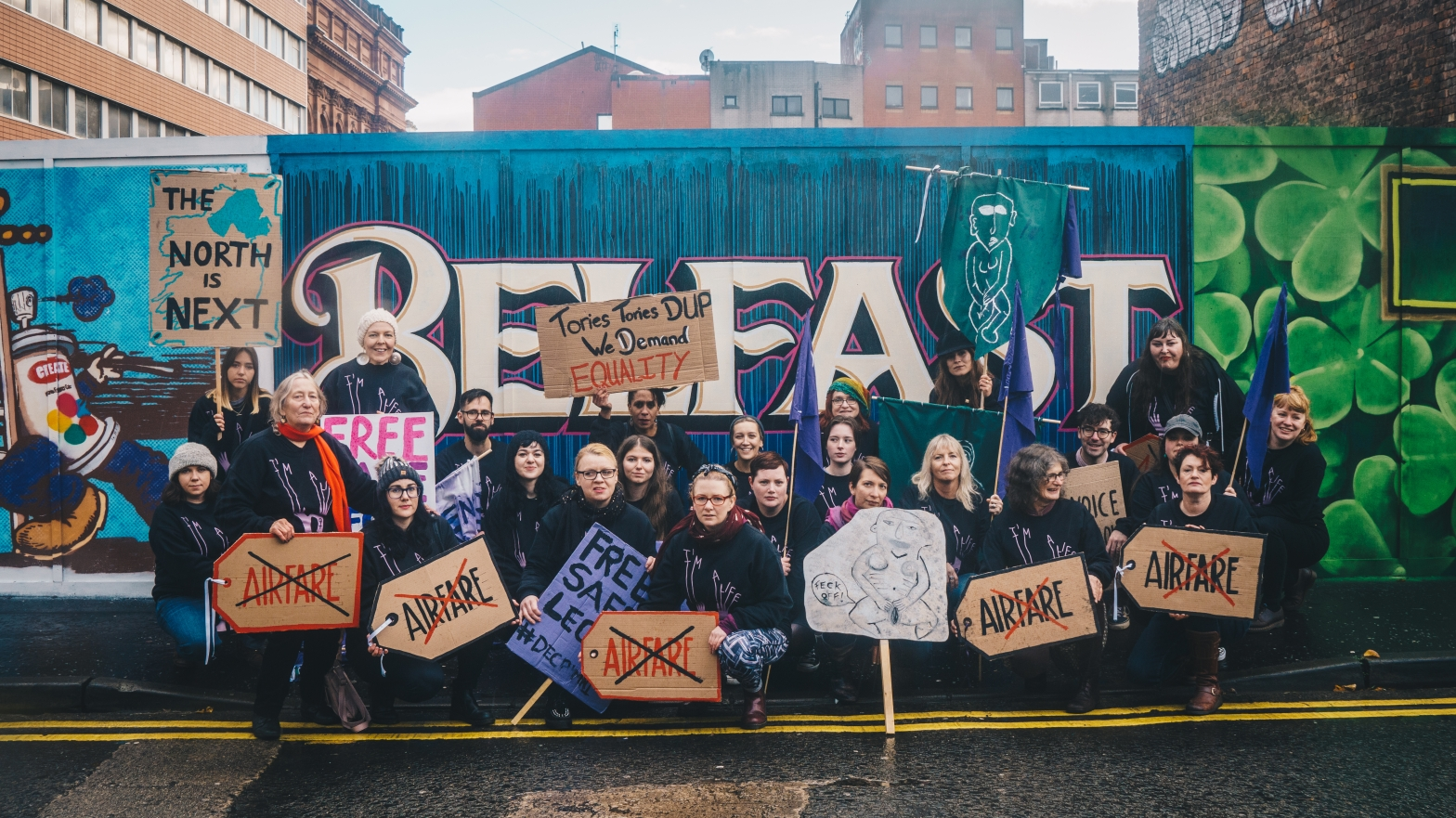Pro-Choice Abortion rights campaigners holding signs in front of a Belfast mural