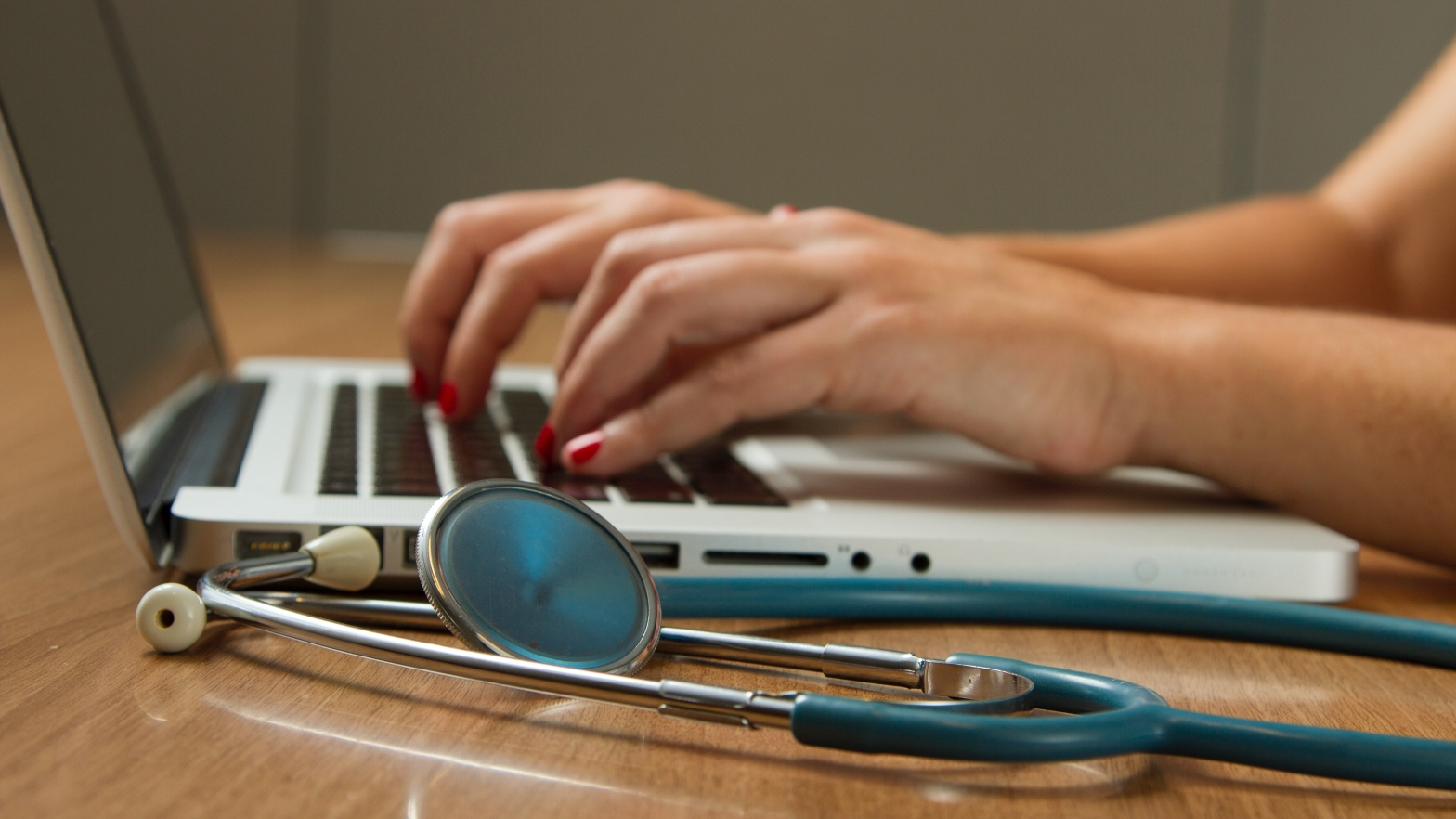 nurse typing on laptop, with stethoscope next to her