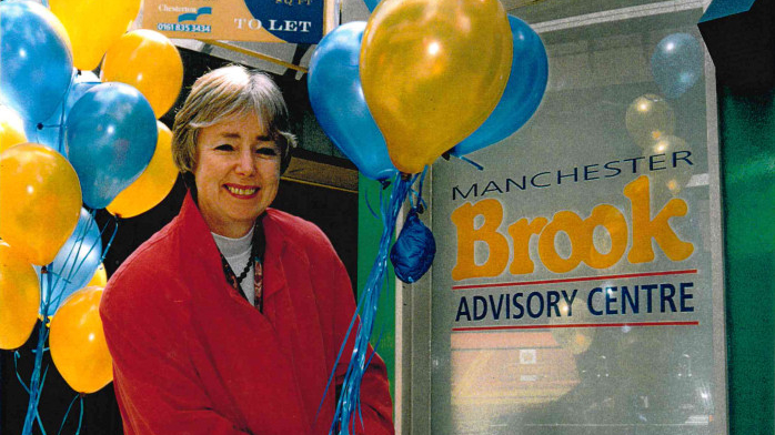 A smiling woman with grey hair stands with blue and gold baloons next to a sign that reads 'Manchester Brook Advisory Centre' in the same colours.