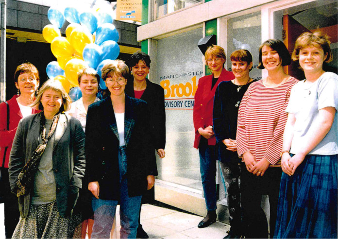 A group of people stand next to the new Brook Manchester Advisory Centre, smiling with blue and yellow baloons.