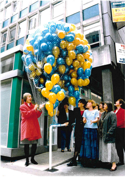 A woman with grey hair and a red coat removes the net from a huge bunch of blue and yellow balloons while other people smile and clap next to her.