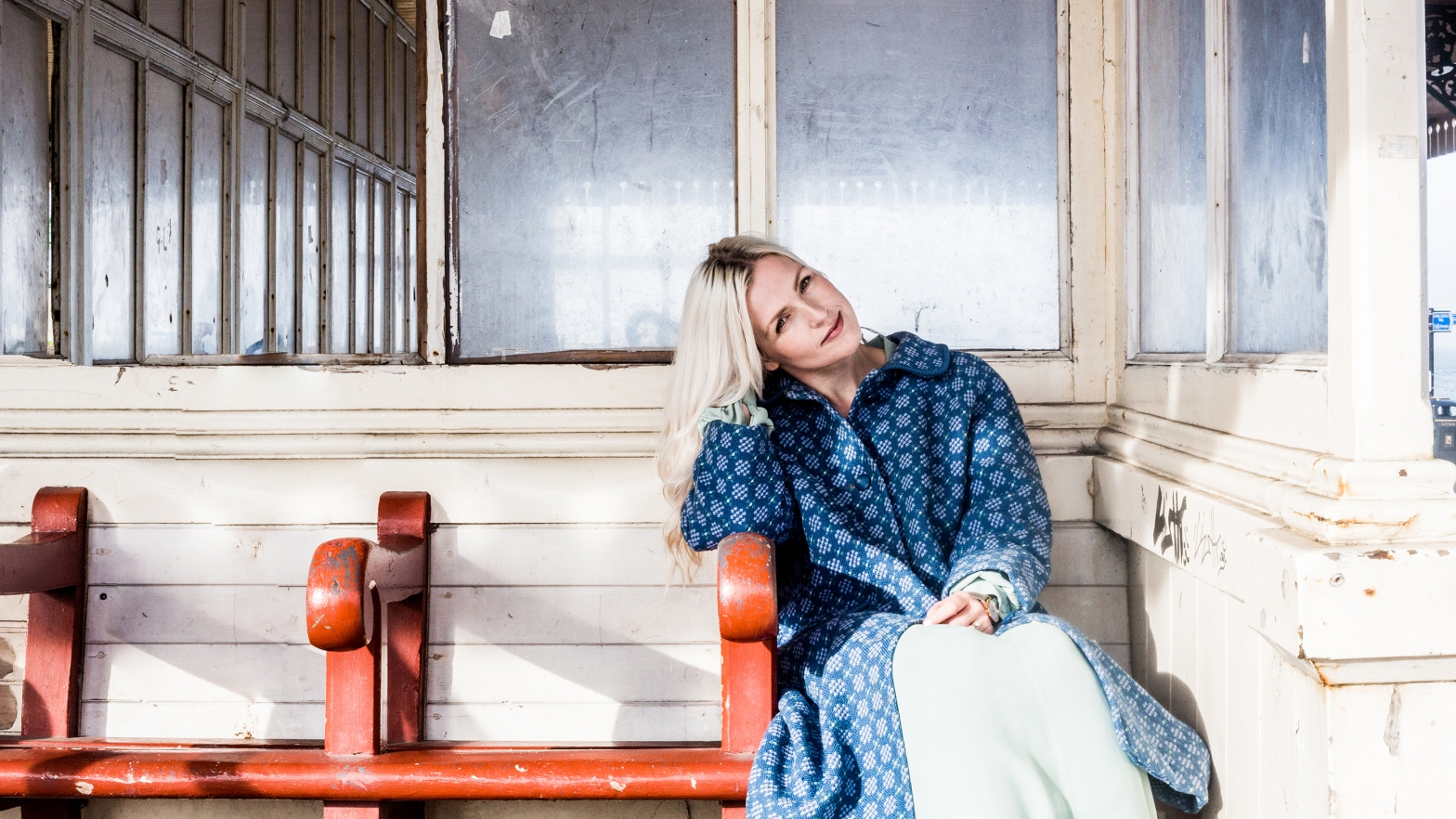 photo of Jenefer Odell sitting on a bench, wearing a blue coat and smiling
