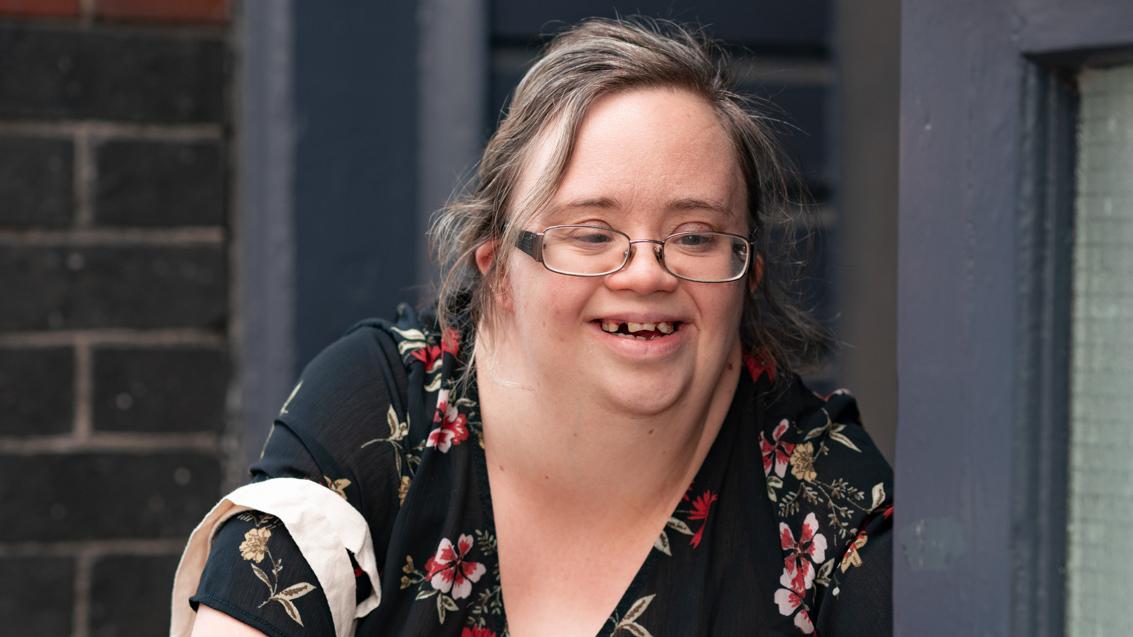 Ellen Goodey smiling, with her hands clasped on her knee.