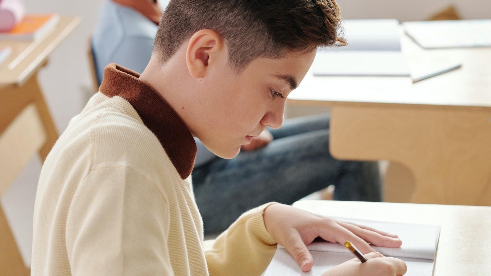 a boy in school writing something down